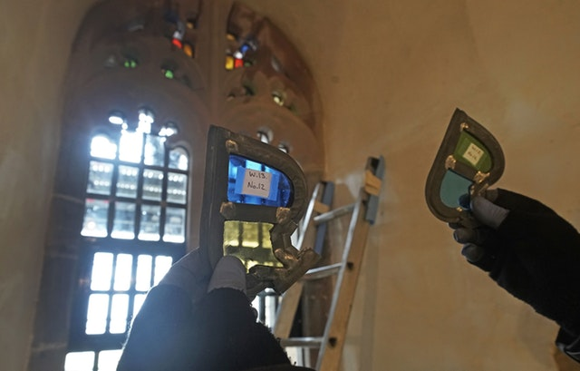 Stained glass window parts are held up to the light as restoration work is carried out (Owen Humphreys/PA)