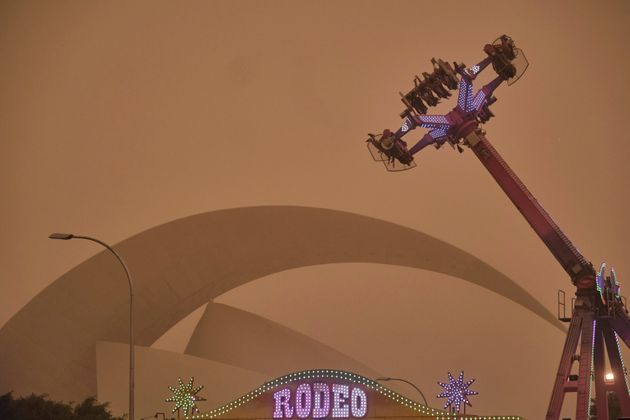People ride on a fairground attraction in a cloud of red dust in Santa Cruz de