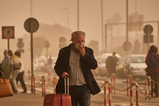 A passenger covers his nose and mouth in a cloud of red dust at the airport in Santa Cruz de
