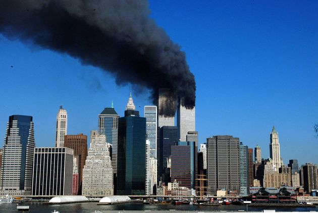 The twin towers of the World Trade Center billow smoke after hijacked airliners crashed into them early...
